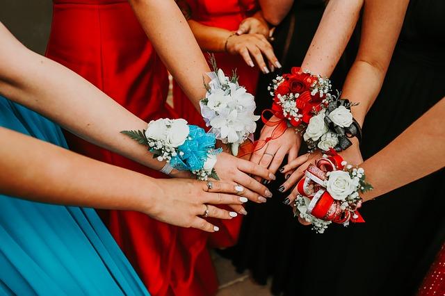 Maturantky ve společenských šatech stojící s nataženýma rukama v kruhu.jpg