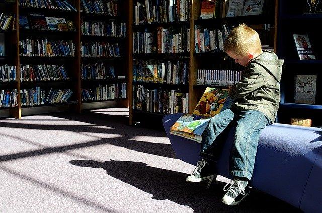 Dítě čte v knihovně