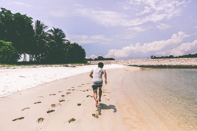 muž běží na pláži